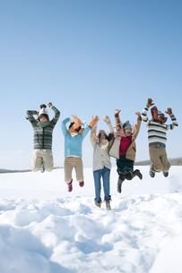 雪原でジャンプをする若者たちの写真素材 [FYI04544306]