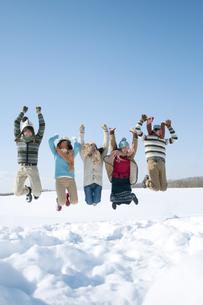 雪原でジャンプをする若者たちの写真素材 [FYI04544308]