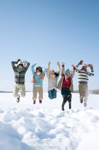 雪原でジャンプをする若者たちの写真素材 [FYI04544309]