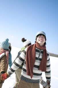 雪原で手をつなぐ若者たちの写真素材 [FYI04544362]