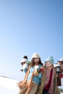 雪原でおしくらまんじゅうをする若者たちの写真素材 [FYI04544369]