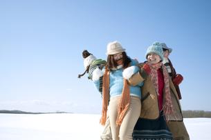 雪原でおしくらまんじゅうをする若者たちの写真素材 [FYI04544373]