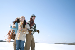 雪原でおしくらまんじゅうをする若者たちの写真素材 [FYI04544374]