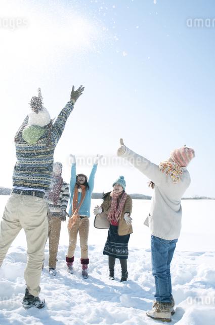 雪原で雪を舞い上げる若者たちの写真素材 [FYI04544407]