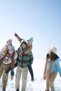 雪原でおんぶをする若者たちの写真素材 [FYI04544409]