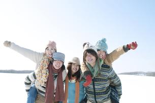 雪原でおんぶをする若者たちの写真素材 [FYI04544410]