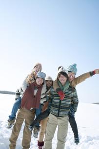 雪原でおんぶをする若者たちの写真素材 [FYI04544411]
