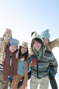 雪原でおんぶをする若者たちの写真素材 [FYI04544414]