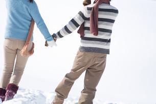 雪原で手をつなぐカップルの後姿の写真素材 [FYI04544451]