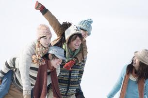 雪原でおんぶをする若者たちの写真素材 [FYI04544452]