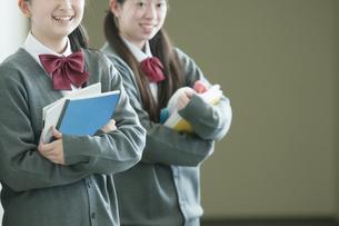 勉強道具を持ち微笑む中学生の写真素材 [FYI04544471]