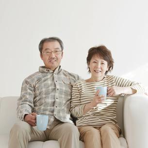 ソファーで微笑むシニア夫婦の写真素材 [FYI04544507]