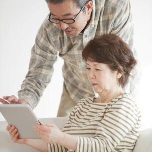 タブレットPCの画面を見るシニア夫婦の写真素材 [FYI04544549]