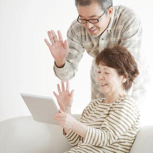 タブレットPCの画面を見るシニア夫婦の写真素材 [FYI04544555]