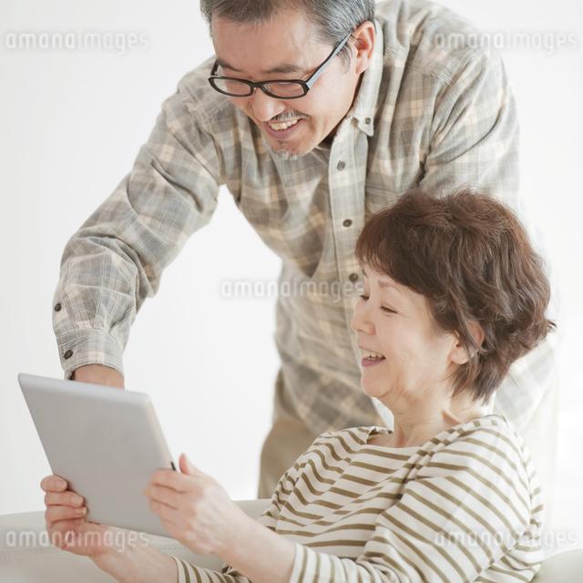 タブレットPCの画面を見るシニア夫婦の写真素材 [FYI04544558]