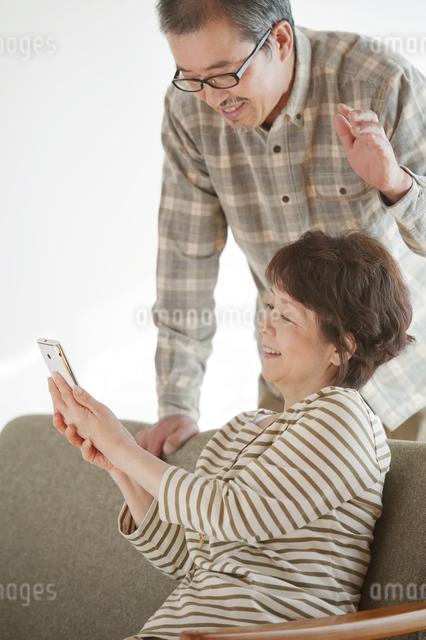 スマートフォンの画面を見るシニア夫婦の写真素材 [FYI04544563]