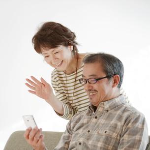スマートフォンの画面を見るシニア夫婦の写真素材 [FYI04544566]