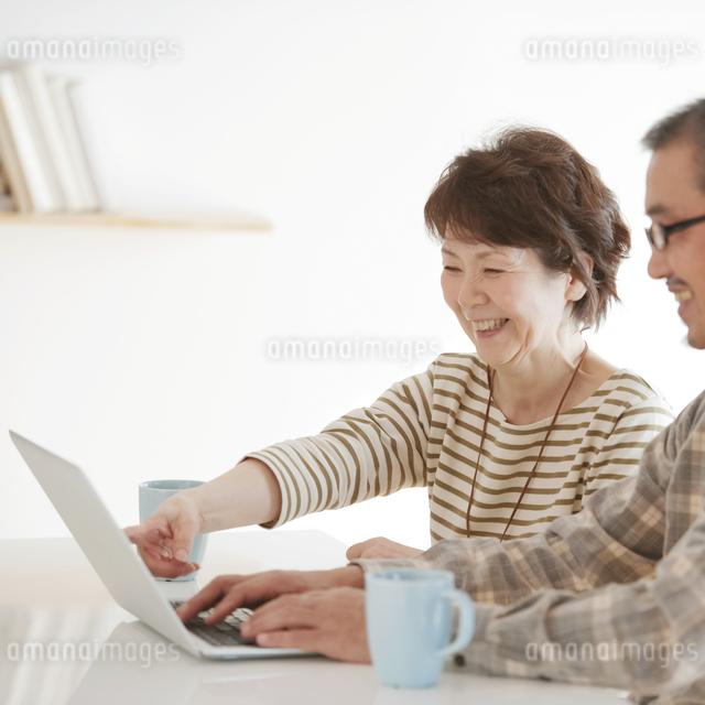 パソコンをするシニア夫婦の写真素材 [FYI04544569]