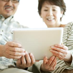 タブレットPCの画面を見るシニア夫婦の写真素材 [FYI04544604]