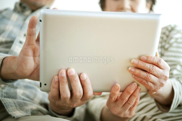 タブレットPCを持つシニア夫婦の手元の写真素材 [FYI04544606]