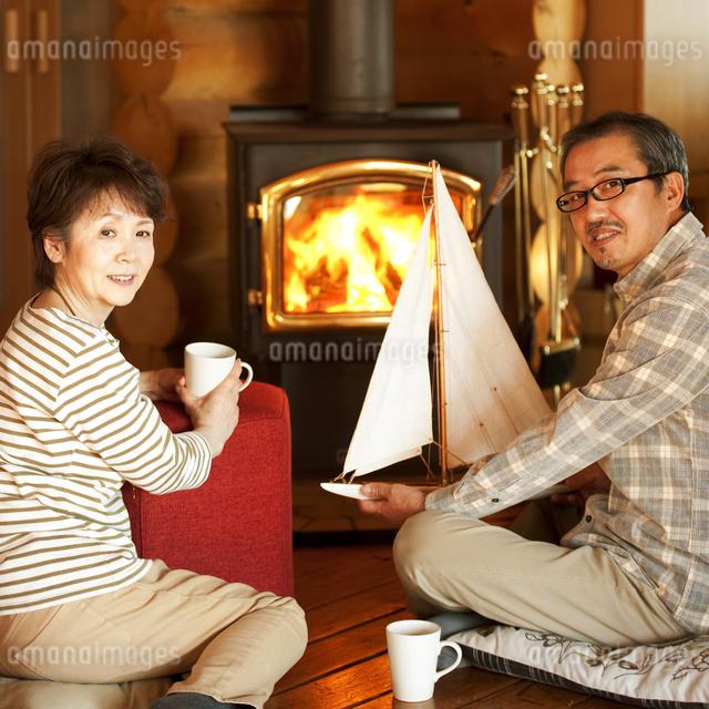 暖炉の前でくつろぐシニア夫婦の写真素材 [FYI04544609]