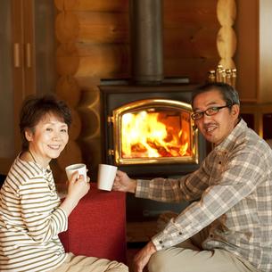 暖炉の前でくつろぐシニア夫婦の写真素材 [FYI04544610]