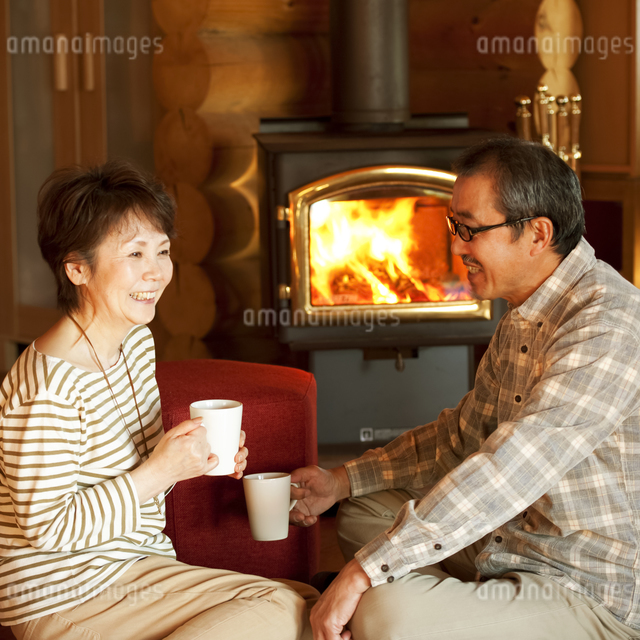 暖炉の前でくつろぐシニア夫婦の写真素材 [FYI04544611]