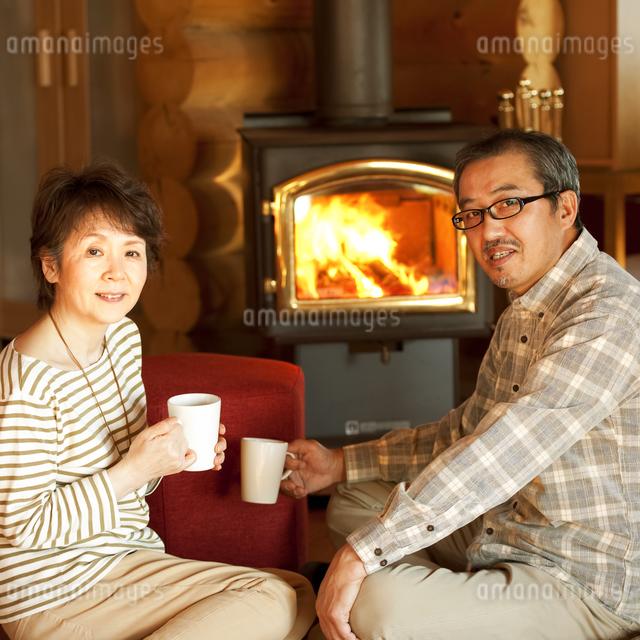 暖炉の前でくつろぐシニア夫婦の写真素材 [FYI04544612]