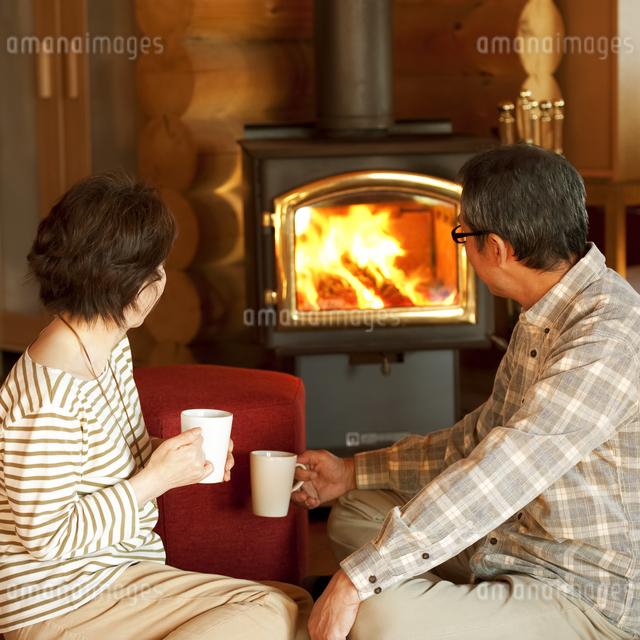 暖炉の前でくつろぐシニア夫婦の写真素材 [FYI04544613]