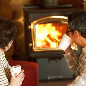 暖炉の前でくつろぐシニア夫婦の写真素材 [FYI04544614]