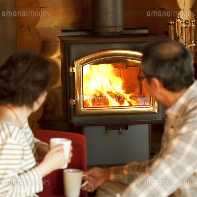 暖炉の前でくつろぐシニア夫婦の写真素材 [FYI04544615]