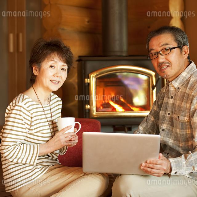暖炉の前でパソコンをするシニア夫婦の写真素材 [FYI04544616]