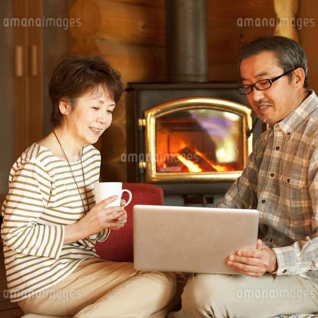 暖炉の前でパソコンをするシニア夫婦の写真素材 [FYI04544617]