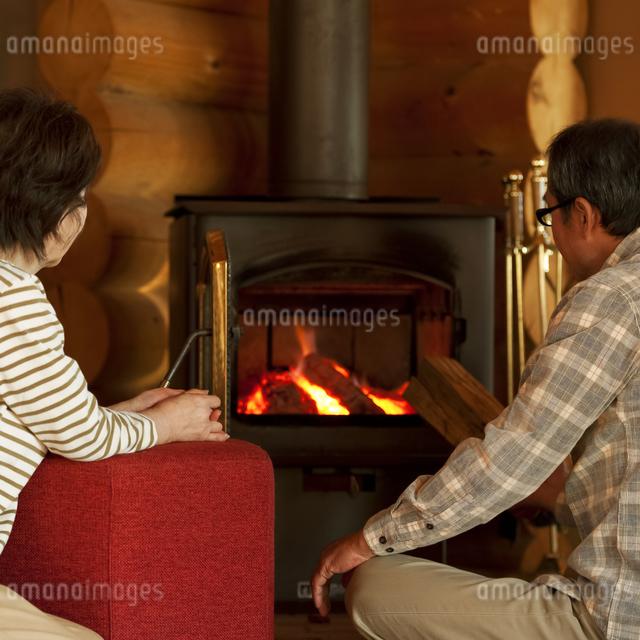 暖炉の前でくつろぐシニア夫婦の写真素材 [FYI04544618]