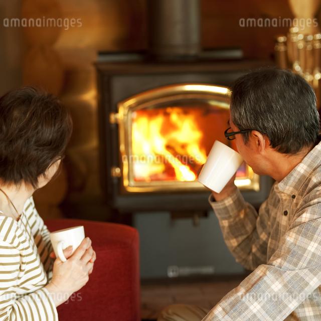 暖炉の前でくつろぐシニア夫婦の写真素材 [FYI04544619]
