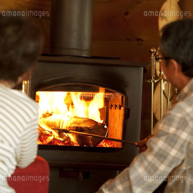 暖炉の前でくつろぐシニア夫婦の写真素材 [FYI04544620]