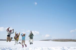 雪原でジャンプをする若者たちの写真素材 [FYI04544622]
