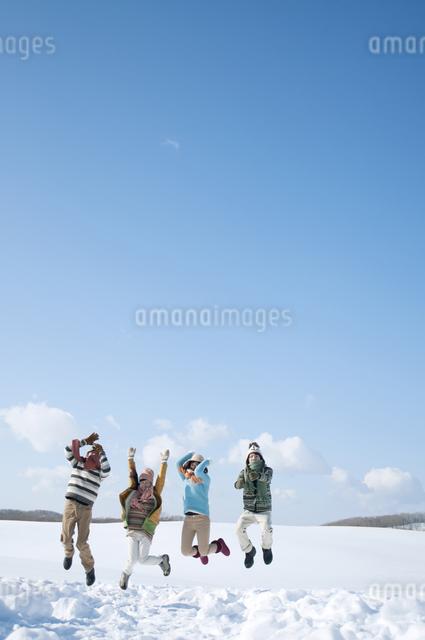 雪原でジャンプをする若者たちの写真素材 [FYI04544624]