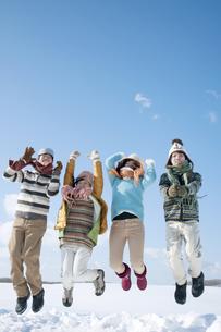 雪原でジャンプをする若者たちの写真素材 [FYI04544625]