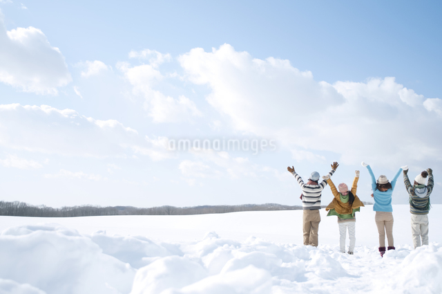 雪原で両手を広げる若者たちの後姿の写真素材 [FYI04544658]