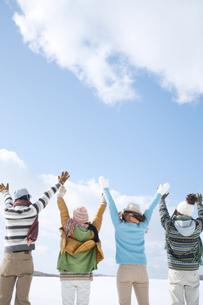 雪原で両手を広げる若者たちの後姿の写真素材 [FYI04544667]