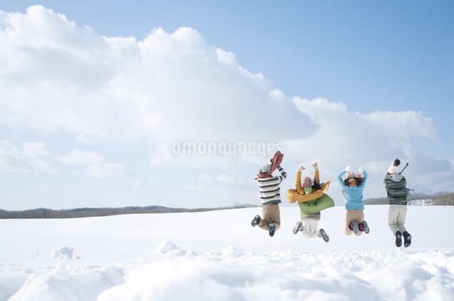 雪原でジャンプをする若者たちの後姿の写真素材 [FYI04544675]