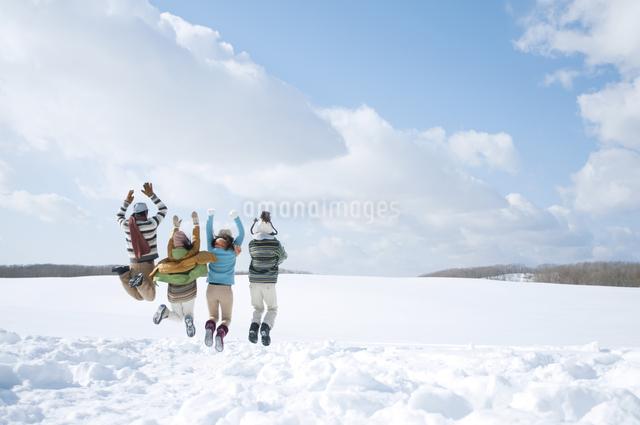 雪原でジャンプをする若者たちの後姿の写真素材 [FYI04544677]