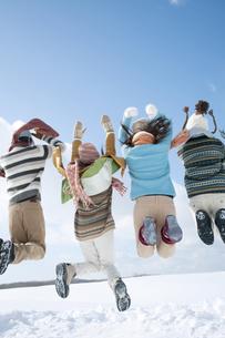 雪原でジャンプをする若者たちの後姿の写真素材 [FYI04544678]