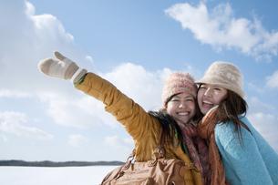 雪原で微笑む2人の女性の写真素材 [FYI04544690]