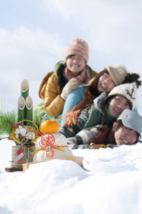 雪原で積み重なる若者たちと正月グッズの写真素材 [FYI04544734]