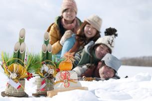 雪原で積み重なる若者たちと正月グッズの写真素材 [FYI04544735]