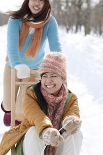 そりで遊ぶ2人の女性の写真素材 [FYI04544767]