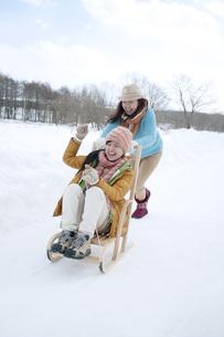そりで遊ぶ2人の女性の写真素材 [FYI04544778]