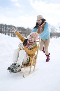 そりで遊ぶ2人の女性の写真素材 [FYI04544780]